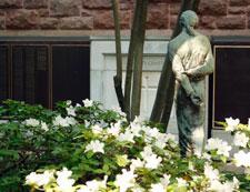 Statue of Jesus Christ in a memorial garden with white azaleas.